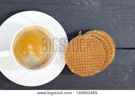 Dutch cookie stroopwafels with cup of coffee on black wooden background