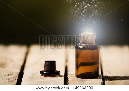 Small brown medicine bottle for magicians remedy, animated star dust coming out from top , sitting on wooden surface.