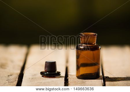 Small brown medicine bottle for magicians remedy, black cap lying next to it on wooden surface.
