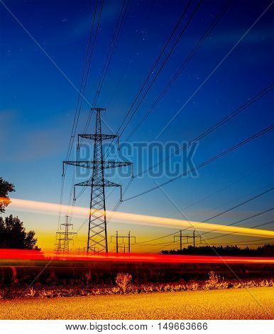 Long Exposure Red Car light trails on a road on blue hour with electrical power lines and pylons disappear over the horizon