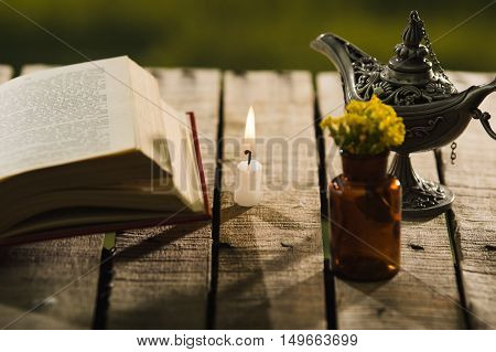 Thick book lying open on wooden surface next to small brown bottle with yellow flowers and Aladin style lamp, beautiful night light setting, magic concept shoot.