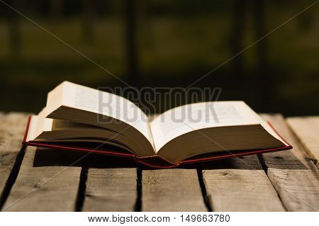 Thick book lying open on wooden surface, beautiful night light setting, magic concept shoot.