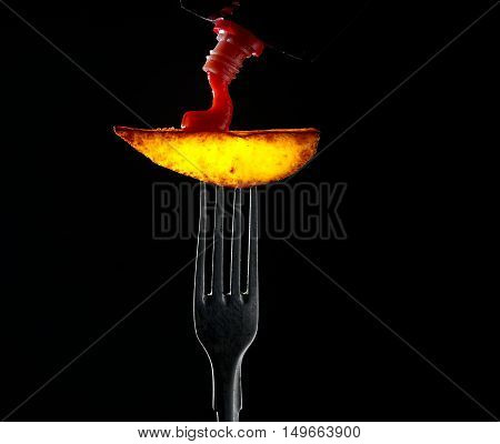 French fries on a fork on a black background