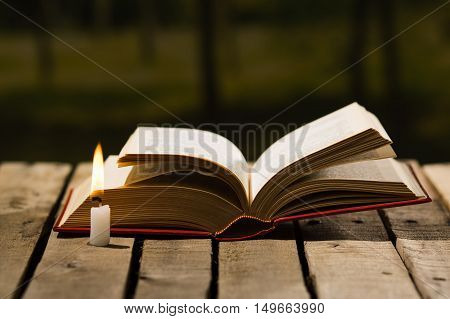 Thick book lying open on wooden surface, wax candle sitting next to it, beautiful night light setting, magic concept shoot.