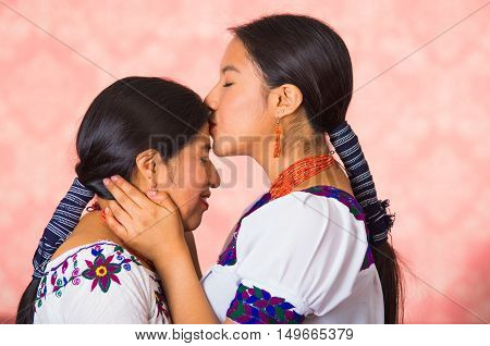 Beautiful hispanic mother and daughter wearing traditional andean clothing, seen from profile angle facing each other, young woman kissing her mom on forehead, pink studio background.