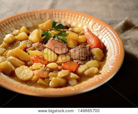 Fresh beef stew, potatoes, greens, original spices in ceramic dish