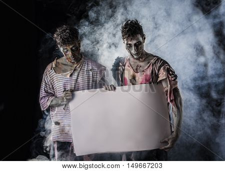 Two Male Zombies Holding Empty White Banner on Dark Background and Smoke