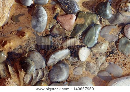 stones which lie in the water and shimmer with rainbow colors