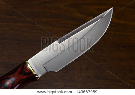 shiny hunting knife on a wooden table