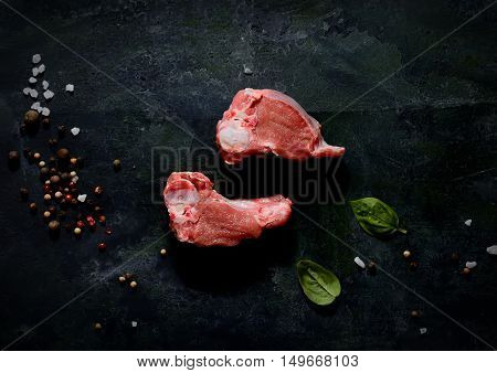 pieces of fresh raw lamb with green leaves on a black background
