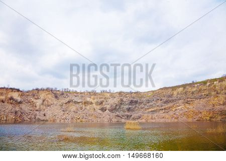 deep quarry with clear water and a steep bank