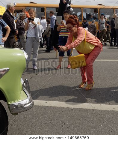 MOSCOW, RUSSIA - August 13, 2016: Bent woman studiously photographing an retro car. August 13, 2016 in Moscow, Russia