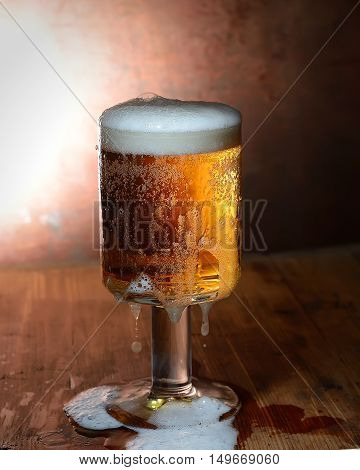 glass of beer with foam on a wooden board