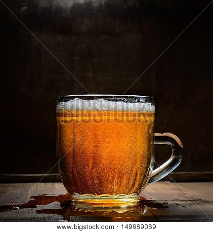 Vintage glass of beer with foam on a wooden board