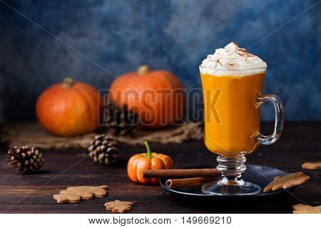 Pumpkin spice latte, smoothie, Boozy cocktail with whipped cream on top on a wooden background. Copy space