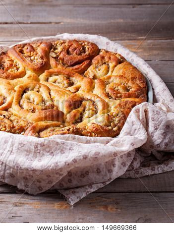 Cinnamon rolls in a baking dish on wooden background