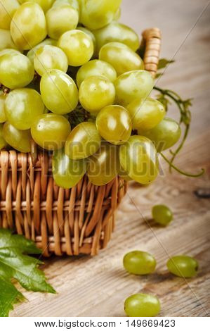 Cluster grapes in wicker basket with leaf at wooden rustic style