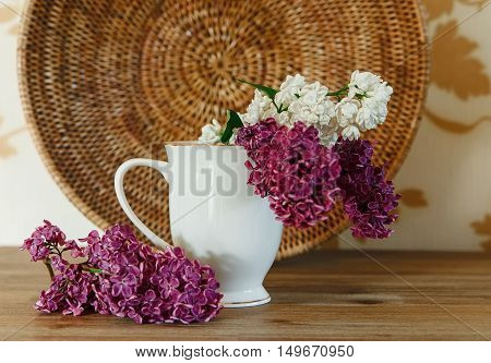 Two Branch of White and Purple Lilac in the Ceramic Cup.Rottan Plate.Wooden Background.Selective Focus