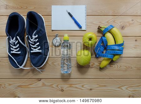Fitness concept with sneakers notebook apple dumbbells stopwatch and measure tape