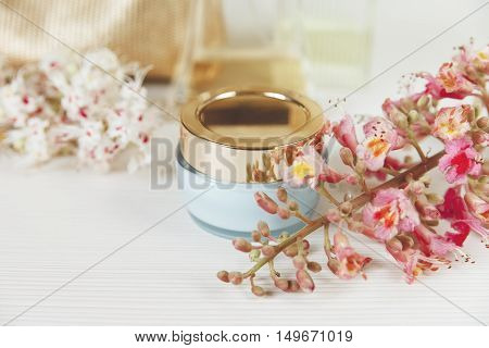 There White and Pink Branches of Chestnut Tree.Blue Bottle Cream with Gold Cover are on White Table.Selective Focus