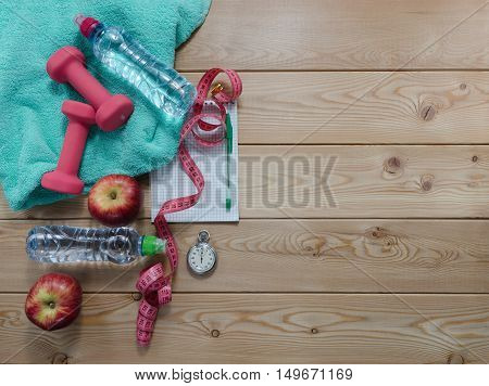 Fitness concept with towel. bottle of water measure tape apples dumbbells and stopwatch.