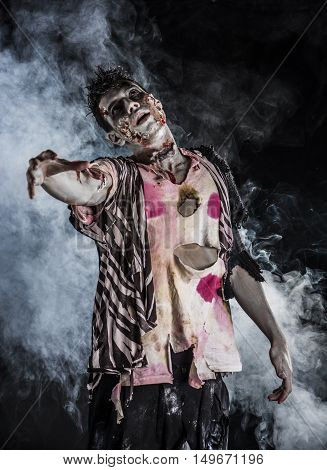 Male zombie standing on black smoky background, reaching hand towards camera