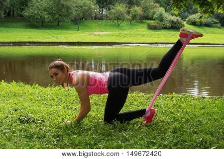 Attractive young woman. Athlete girl doing Stretching exercises for legs with rubber tape