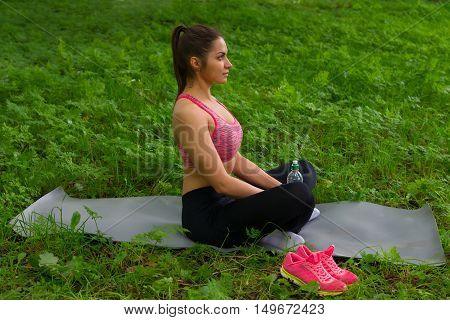 Young beautiful woman doing yoga exercises in park after sports training