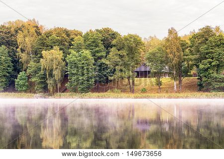 Wooden house at the Lake in foggy autumn morning