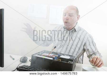 Mature businessman blowing smoke emerging from computer chassis in office