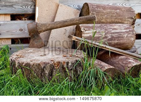 Old ax in the wooden, cracked tree stump on a background of chopped firewood . Preparing for cold winter days.