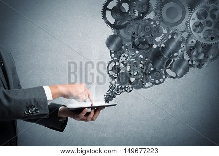Businessman touch a tablet screen with gears mechanism