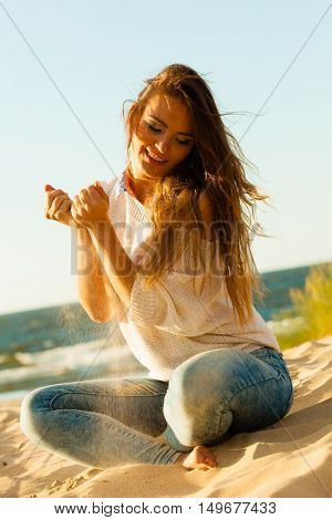 Joy and carefree. Gorgeous long haired woman having fun with sand on beach. Young joyful attractive girl feels freedom.