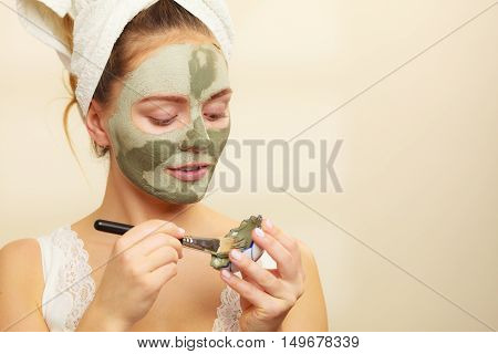 Woman Applying With Brush Clay Mud Mask To Her Face