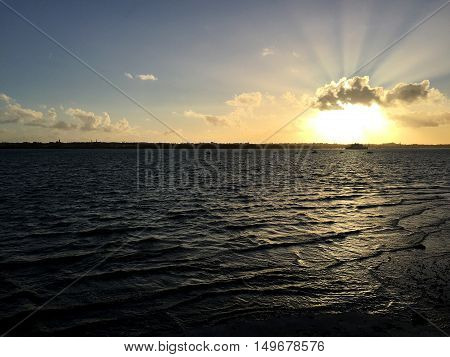 Sunset at sea with land and boats in the background. Space for text.