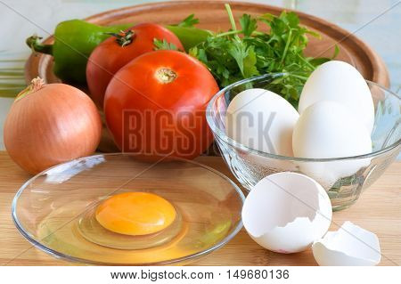 White eggs, a cracked egg, tomato, onion, green pepper are ready for cooking meal. Egg yolk in a plate.