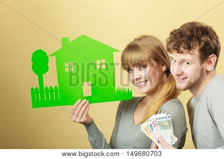 Symbolism property ownership finances mortgage savings concept. Wife and husband holding items. Young couple shows cash with house cutout.