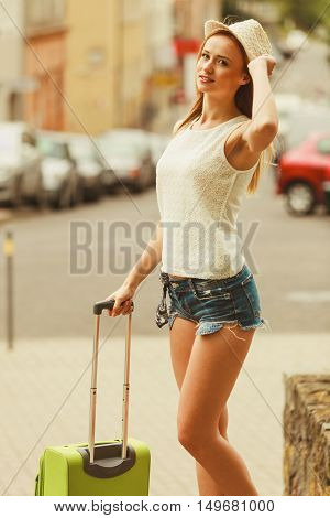 Holidays and vacation. Young smiling girl enjoy her freedom and summer time by travelling visiting other country city. Attractive woman with green suitcase.