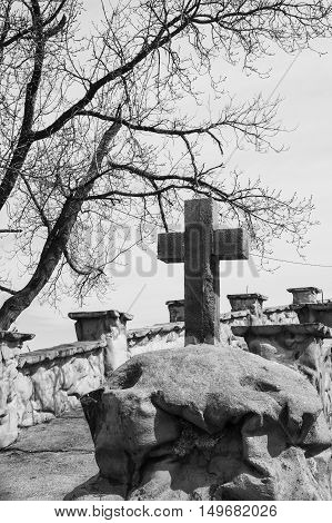 black and white vertical image of a stone cross sitting on a rock with a bare tree beside it.