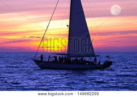Sailboat sunset is a boat full of people sailing along the ocean water with a vibrant sunset in the background and the moon rising over the sea.