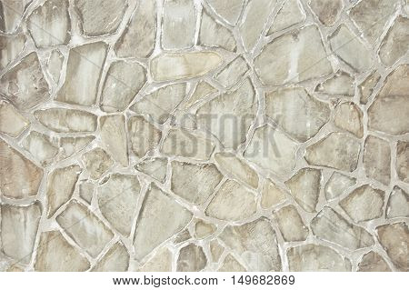 Old grey stone wall background texture close up