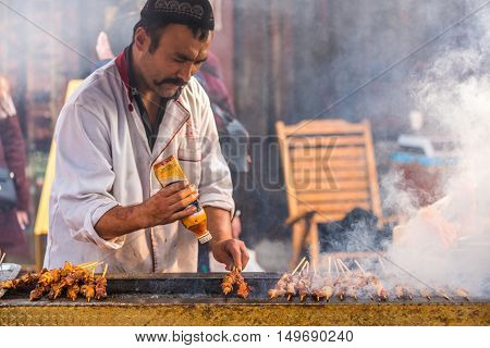 Chengdu Sichuan Province China - Dec 16 2015: A man barbecues lamb skewers near Wenshu monastery