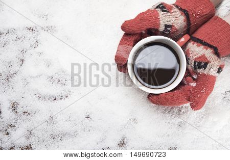 Gloved Hands Holding Hot Coffee Mug. On White Snow