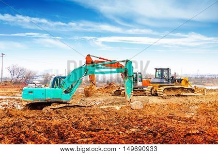 Large excavators and bulldozers at the construction site