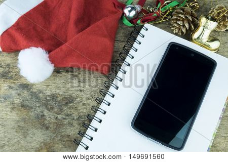 Christmas background. Red headphone in santa Claus hat smart phone and christmas decoration staff on wooden background.
