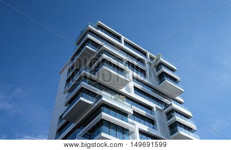 Balconied Apartment Tower Block Beneath Bright Blue Sky at Day