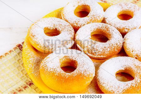 Sweet donuts served on yellow plate. Homemade dessert pastry doughnuts. Hanukkah sweet donuts.