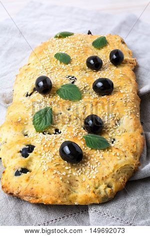 Italian bread with olive garlic and herbs. Homemade traditional Italian bread focaccia on the linen napkin.