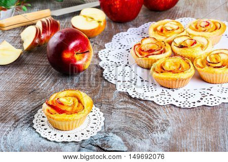 Muffin with rose shaped apple. Sweet apple dessert pie. Homemade apple rose pastry. Breakfast sweet apple muffins.