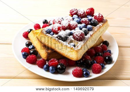Soft waffles with blueberry and raspberry. Breakfast soft waffles with fresh berries. Belgian waffles.